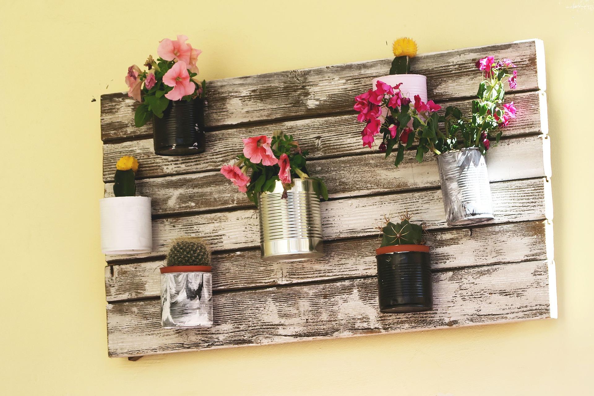 Décoration murale réalisée avec des planches en bois et des plantes dans des conserves