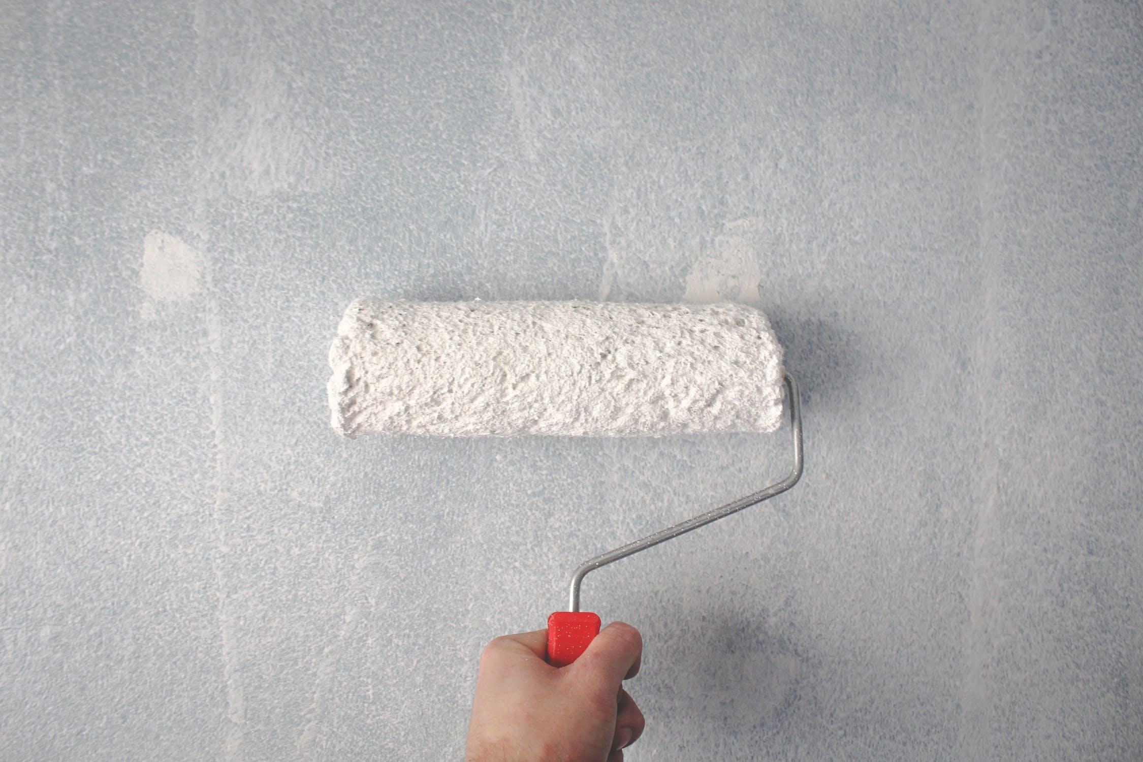 Personne qui applique de la peinture murale avec un rouleau