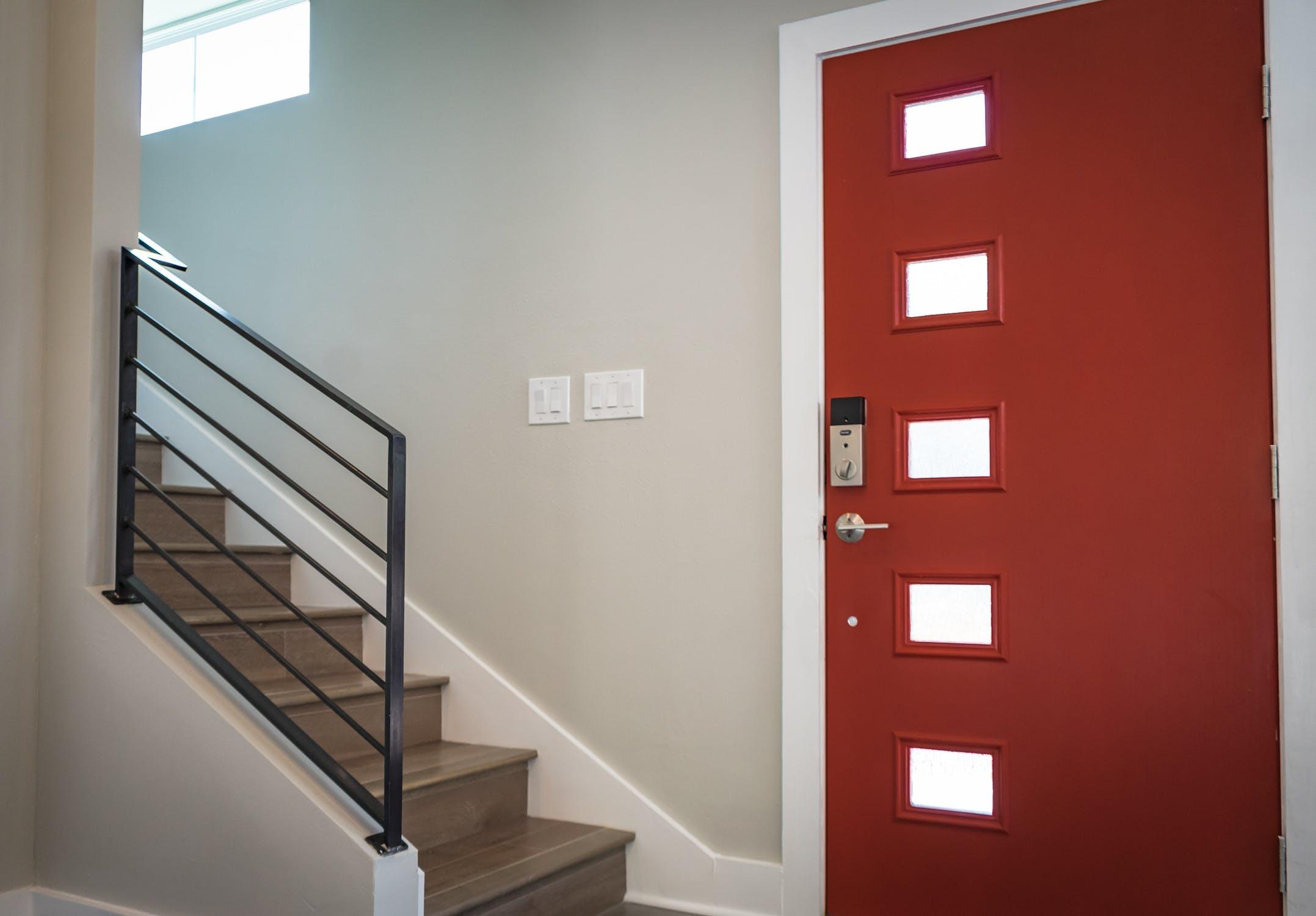 Hall d'entrée moderne avec porte rouge et escaliers contemporains